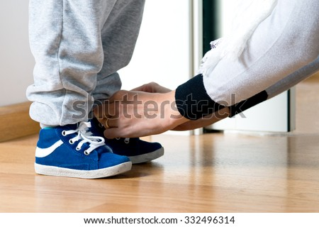 Mother fastens the shoe of his child - stock photo