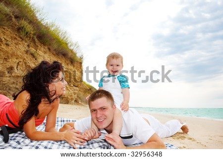 Mother, father and baby boy enjoying their weekend on the beach