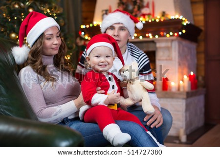 Mother, father and baby in santa red dress smile on a background of Christmas trees in the interior of house