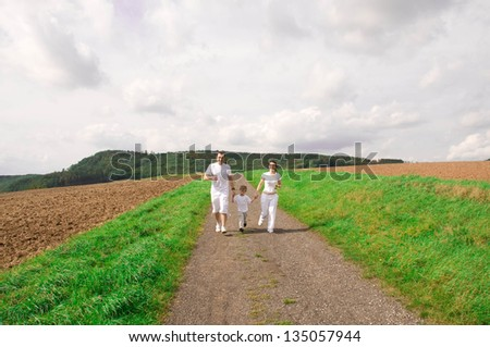 Mother, father and child run down the road. - stock photo