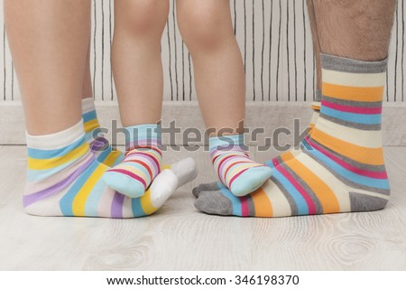 Mother, father and child wearing similar striped socks. Unrecognizable - stock photo