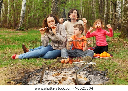 Mother, father and children eat grilled shish kebab outdoor; focus on woman - stock photo