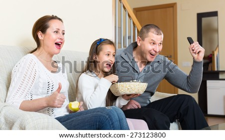 Mother, father and cute girl watching show and smiling indoors. Focus on woman - stock photo