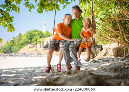 Mother, father and daughter embraces on rope swing under palm trees on tropical beach with lighthouse on back - stock photo