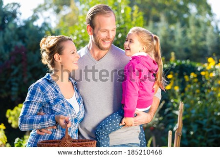 Mother, father and daughter in garden - stock photo