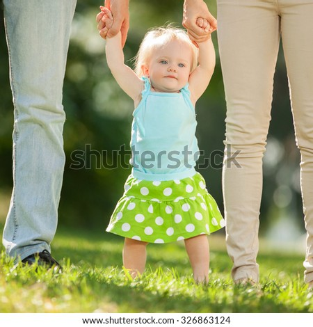Mother, father and daughter in the park. First steps - stock photo