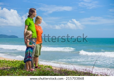Mother, father and daughter on tropical beach holding hands with huge ocean waves on back - stock photo