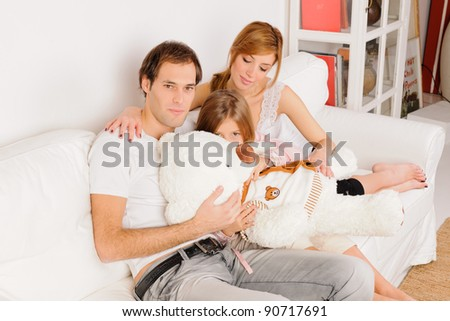 mother, father and daughter playing at home on white sofa