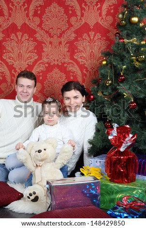 Mother, father and daughter sit on floor with gifts near Christmas tree at home. - stock photo