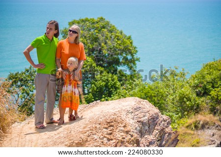 Mother, father and daughter stay on tropical island cliff and look at sea - stock photo