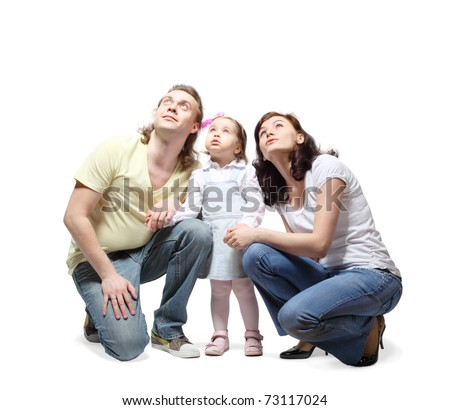 Mother, father and little daughter sit down, hold hands and fixedly looking up - stock photo