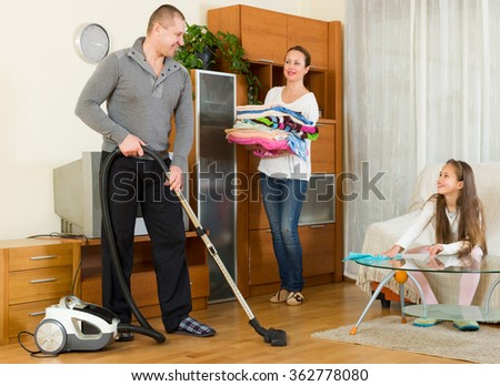 Mother, father and little smiling girl doing general cleaning indoors - stock photo
