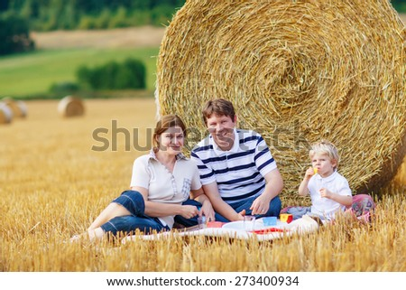Mother, father and little son, kid boy having picnic on yellow hay field in summer, outdoors. Family having fun together. - stock photo