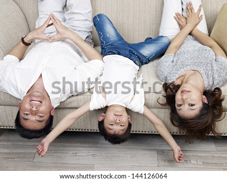mother, father and son having fun at home. - stock photo