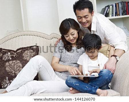 mother, father and son looking at tablet computer. - stock photo