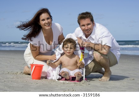 Mother, father and son on a beach - stock photo