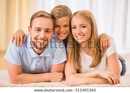 Mother, father and son together. Happy family are smiling to the camera. - stock photo