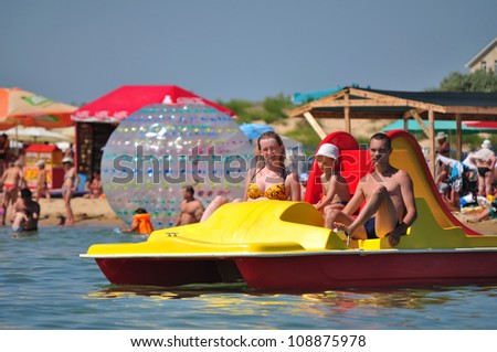 Mother, father and the son float on a catamaran - stock photo