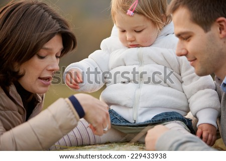 Mother Father and their little baby having happy times together in autumn outdoor in the green wood and grass - stock photo