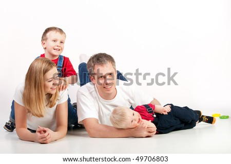 Mother, father and two children lying on the floor and smiling - stock photo