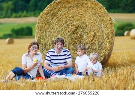 Mother, father and two little children, kid boys having picnic on yellow hay field in summer, outdoors. Family having fun together. - stock photo