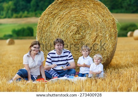 Mother, father and two little children, kid boys picnicking on yellow hay field in summer, outdoors. Family having fun together. - stock photo