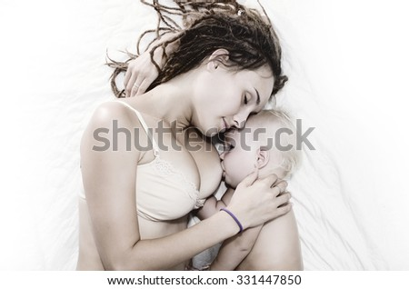Mother feed little baby by breast in the bed. - stock photo