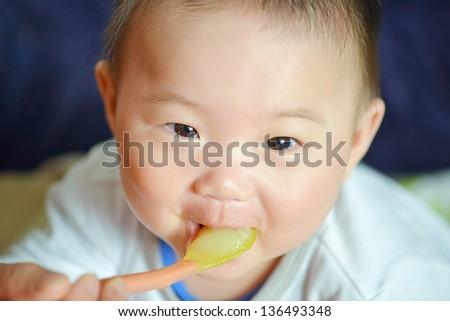 mother feeding baby baby food with a spoon - stock photo