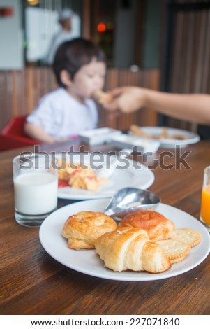 Mother Feeding Baby Boy In High Chair. - stock photo