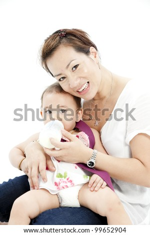 Mother feeding baby daughter - stock photo