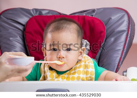 Mother feeding baby food to her child - stock photo