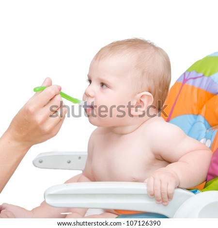 Mother feeding baby food to hungry baby. The kid is eating with big appetite. Isolated on white background with clipping path - stock photo