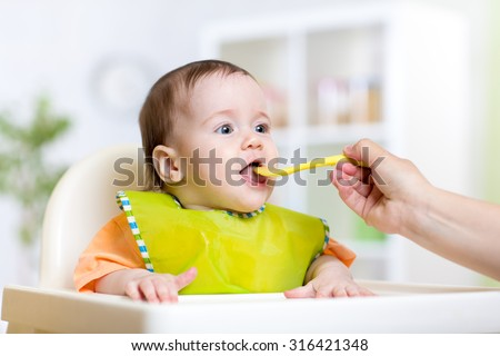 mother feeding baby girl at home kitchen