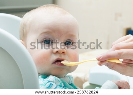 Mother feeding baby in a plastic spoon vegetable puree