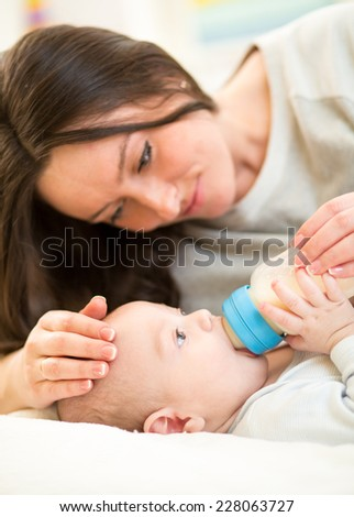 mother feeding baby son with a milk bottle at home