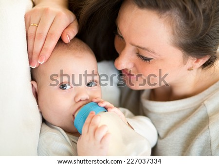 mother feeding baby with a milk bottle - stock photo