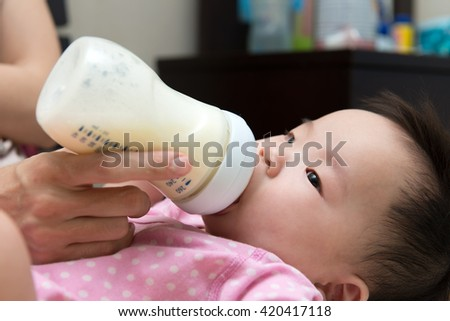 Mother feeding baby with milk from a bottle