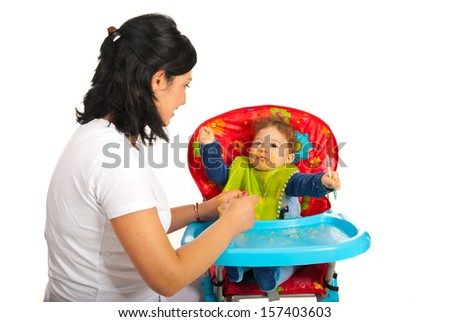 Mother feeding baby with puree in their home