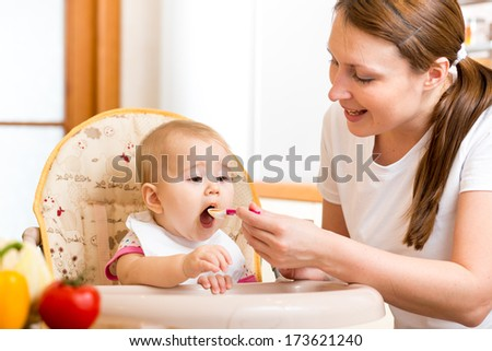 Mother feeding baby with spoon