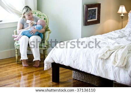Mother feeding bottle to seven month old baby in bedroom - stock photo