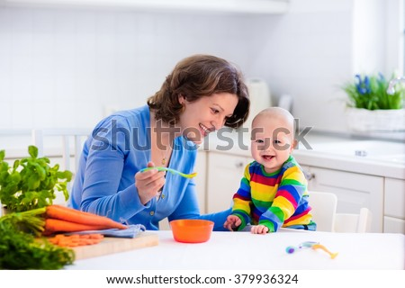 Mother feeding child. First solid food for young kid. Fresh organic carrot for vegetable lunch. Baby weaning. Mom and little boy eat vegetables. Healthy nutrition for children. Parents feed kids. - stock photo