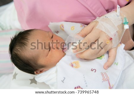 mother feeding cup of milk for newborn baby in patient room . useful when small volumes of breastmilk/colostrum are being given and during emergency situations or mother has problem with her nipple.