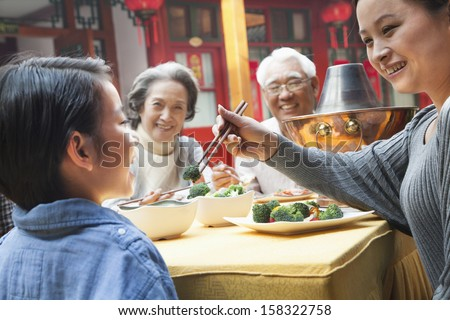 Mother feeding daughter broccoli during a meal - stock photo