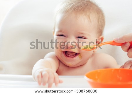Mother feeding daughter puree - stock photo