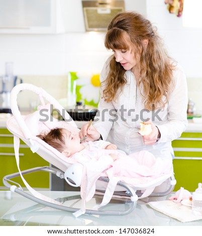 mother feeding her baby apple puree  - stock photo