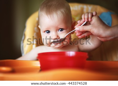 mother feeding her baby boy with a spoon - stock photo