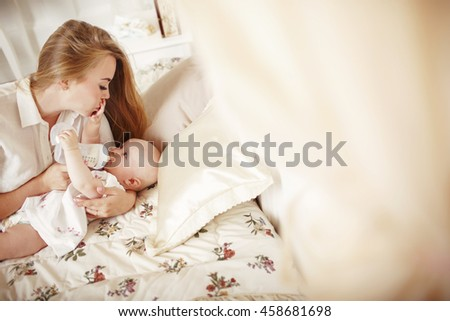 Mother feeding her baby from the bottle. Young woman feeding her baby in bedroom