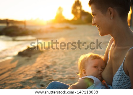 mother feeding her baby in nature outdoor - stock photo