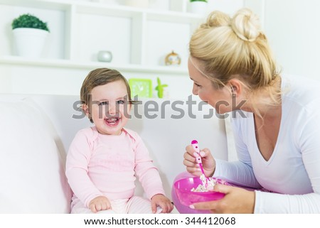Mother feeding her baby little girl with a cake.Baby smiling and like that sweet taste.Shallow doff - stock photo