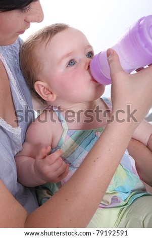 Mother feeding her baby water from a large baby bottle - stock photo